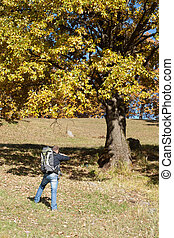Autumn landscape - Photographer taking picture with foliage