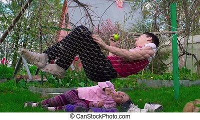 The girl shakes her hammock with a young man outdoors...