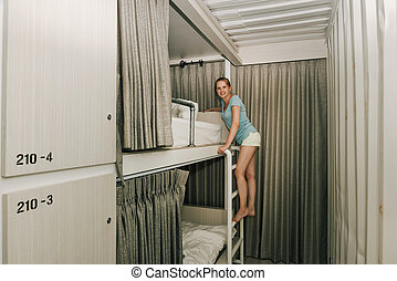 Girl standing in a stylish hostel bedroom - Young woman...