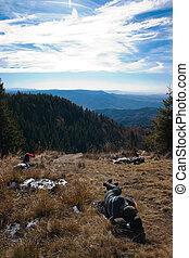 Tourists on mountain top - Tourists taking a nap on top of a...