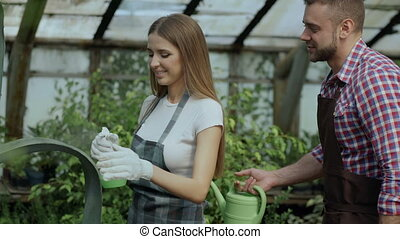 Happy young florist couple in apron have fun while working in greenhouse. Laughing woman spray water in husband face and embrace and kiss him