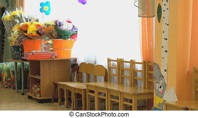 Chairs, table, flowers. Interior of kindergarten