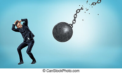 A small businessman trying to hide and cover himself from a falling wrecking ball with a torn chain.