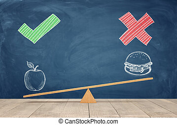 A wooden seesaw on blue chalkboard background where a painted apple overweighs a sandwich.