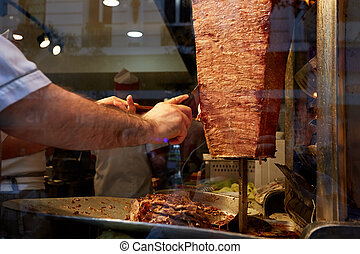 An arm moving to cut the kebab meat.