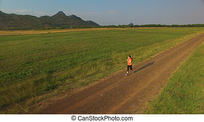 Aerial view of woman running on a rural road