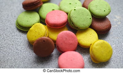 girl takes off the table of macaroon cookies close up