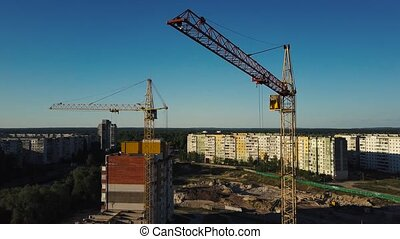 Industrial construction cranes and buildings over sun at...