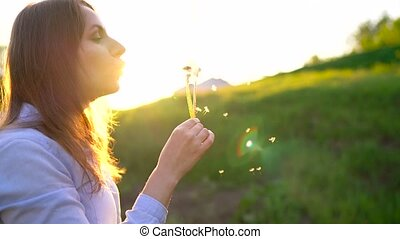 Beauty woman blowing dandelion against the sunset, slow motion