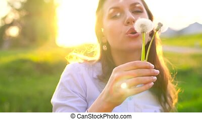 Beauty woman blowing dandelion against the sunset