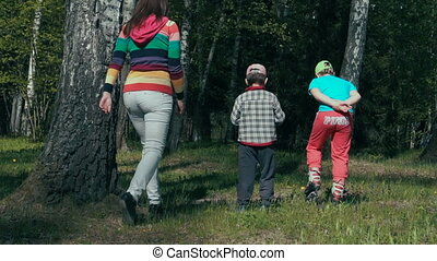 Mother and two children walking in the woods during the...