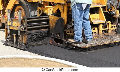 Laying Asphalting - Man stands on an asphalt laying machine...
