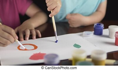 Happy Painting by Two Kids - Kids holding brushes and...