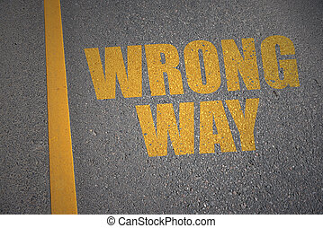asphalt road with text wrong way near yellow line