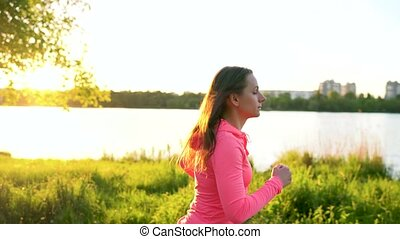 Woman runs through the park on the lake shore at sunset -...
