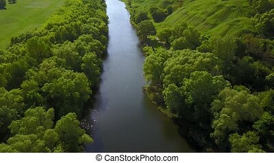 Flight over the Seim River, Ukraine surrounded by trees - aerial videotaping
