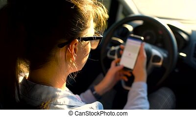 Woman in glasses using a smartphone in the car - Beautiful...