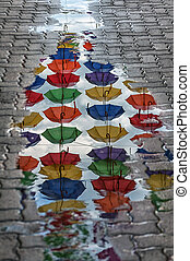 Umbrellas reflection in a puddle - Reflection of umbrellas...