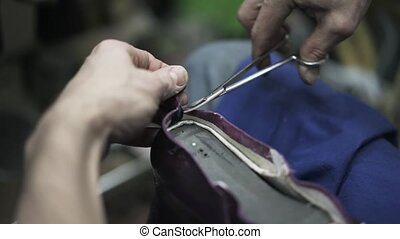 Shoemaker cutting leather with scissors and hammering it -...