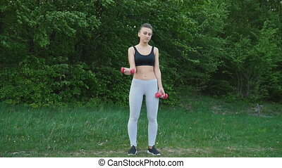 The girl is exercising with a dumbbell
