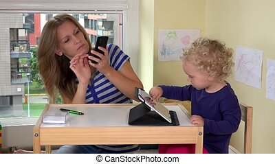 Young pretty woman taking photos of her daughter and herself with smart phone
