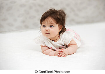 Portrait of baby girl crawling on blanket indoors