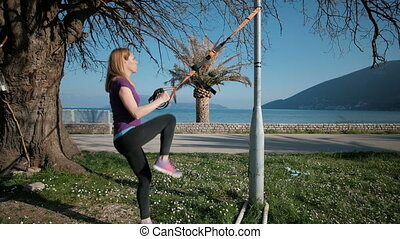 Young woman practicing lunges with TRX loops outdoor....