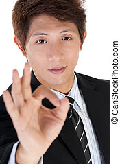 Young executive man give you ok gesture, closeup portrait