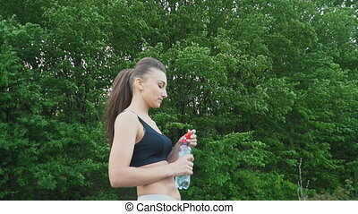 The girl drinks water from a bottle