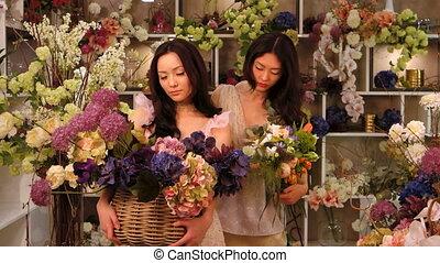 Florists. Asian women happy working in flower store -...