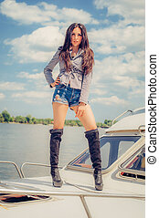 Hot seductive woman in sexy high black boots posing on boat...