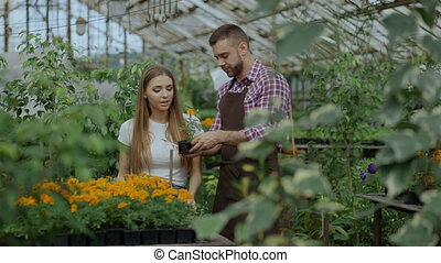 Young cheerful man florist talking to customer and giving...