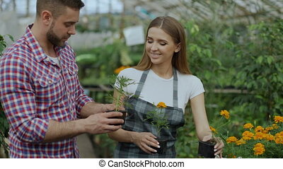 Young friendly woman florist talking to customer and giving...