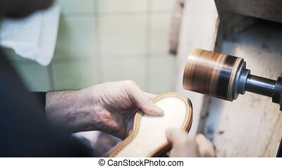 Close up of shoemaker s hands polishing a loafer sole -...