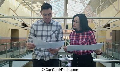 Young man and woman meet in hall in business center to...