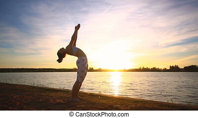 Young woman doing yoga exercises on the lake beach at sunset...