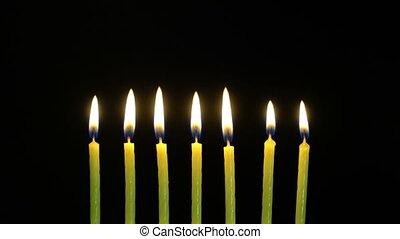 Footage colorful burning candles set on black background. 4k...