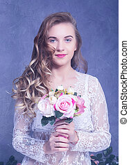 beautiful Girl in a white peignoir with a bouquet of...