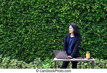 Asian Busineswoman using laptop computer working outside...