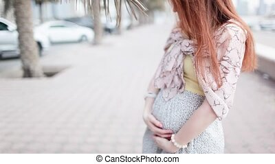 Redhead pregnant girl stroking her belly.