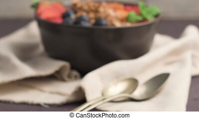 Yogurt with baked granola and berries in small bowl...