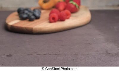 Wooden board with fresh organic fruit and berries:...