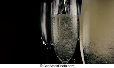 In the foreground a glass of champagne with bubbles out of...