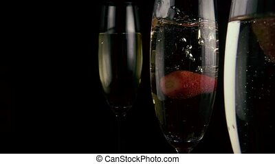 Strawberries fall into a glass with champagne. Slow motion