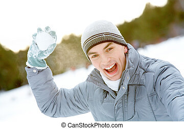 Guy with snowball - Image of attractive young man with...
