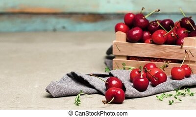 Red ripe cherries in small wooden box on kitchen countertop....
