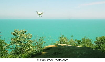 Quadrocopter flies forward from the rock over the sea - 4...