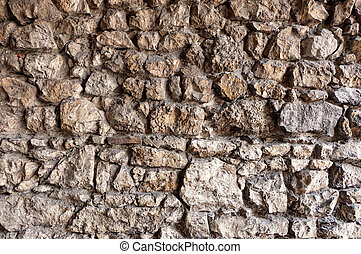 stone wall made of irregular and rough rocks