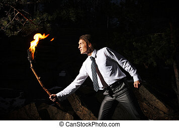 On dangerous way - Image of brave man with burning stick in...