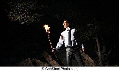 Looking around - Image of brave man holding burning stick...